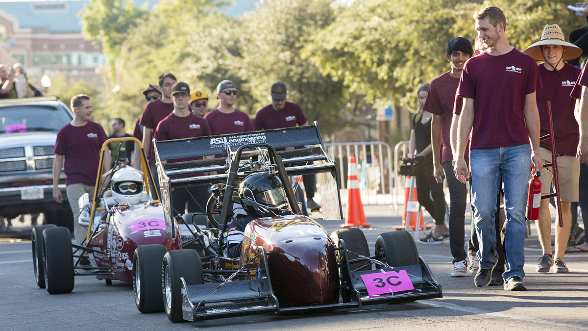Sun Devil Motorsports, the Formula chapter of the Society of Automotive Engineers at ASU, walk the parade route with one of their race cars.