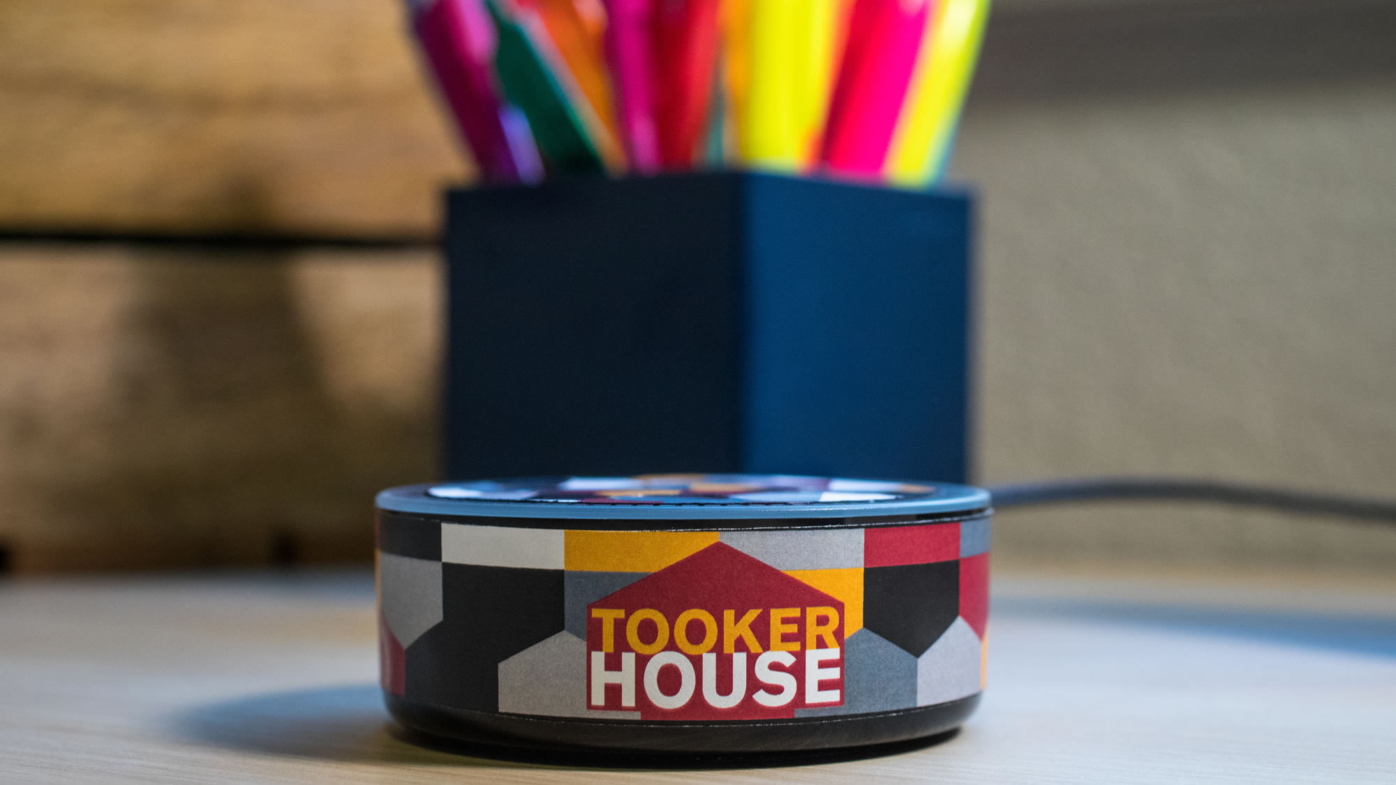 A Tooker House-branded Echo Dot (TM) sits on a desk in front of a box of pencils and highlighters.