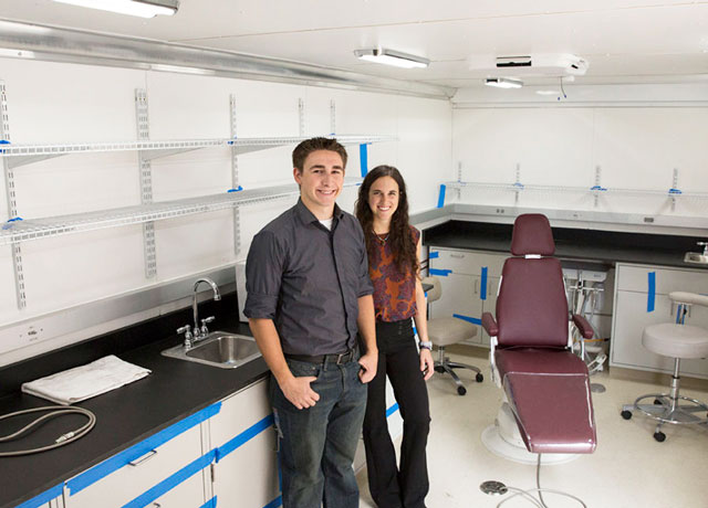 A young man and young woman stand in a pristine white trailer, with laboratory cabinetry and a dental examination chair behind them. The caption reads: Above: Nick Kemme and Sara Mantlik show off the completed mobile dental clinic, which will expand the mission impact of IMAHelps, a nonprofit group that provides dental and medical care to underserved populations in Central and South America. Photographer: Pete Zrioka/ASU