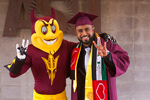 A graduating student poses with Sparky at the Convocation Ceremony.