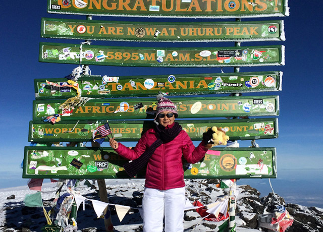 Sophie Olson stands atop Mount Kilimanjaro in Africa at the completion of the first marathon in her seven-continent marathon tour.