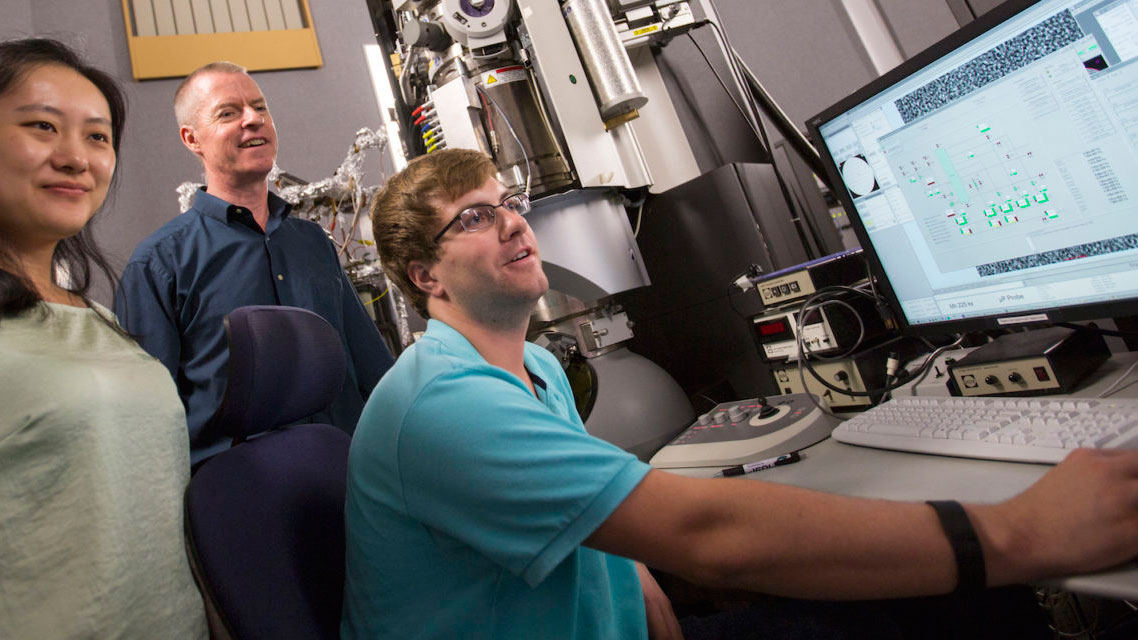 Peter Crozier and two of his graduate students sit at a computer in his lab.