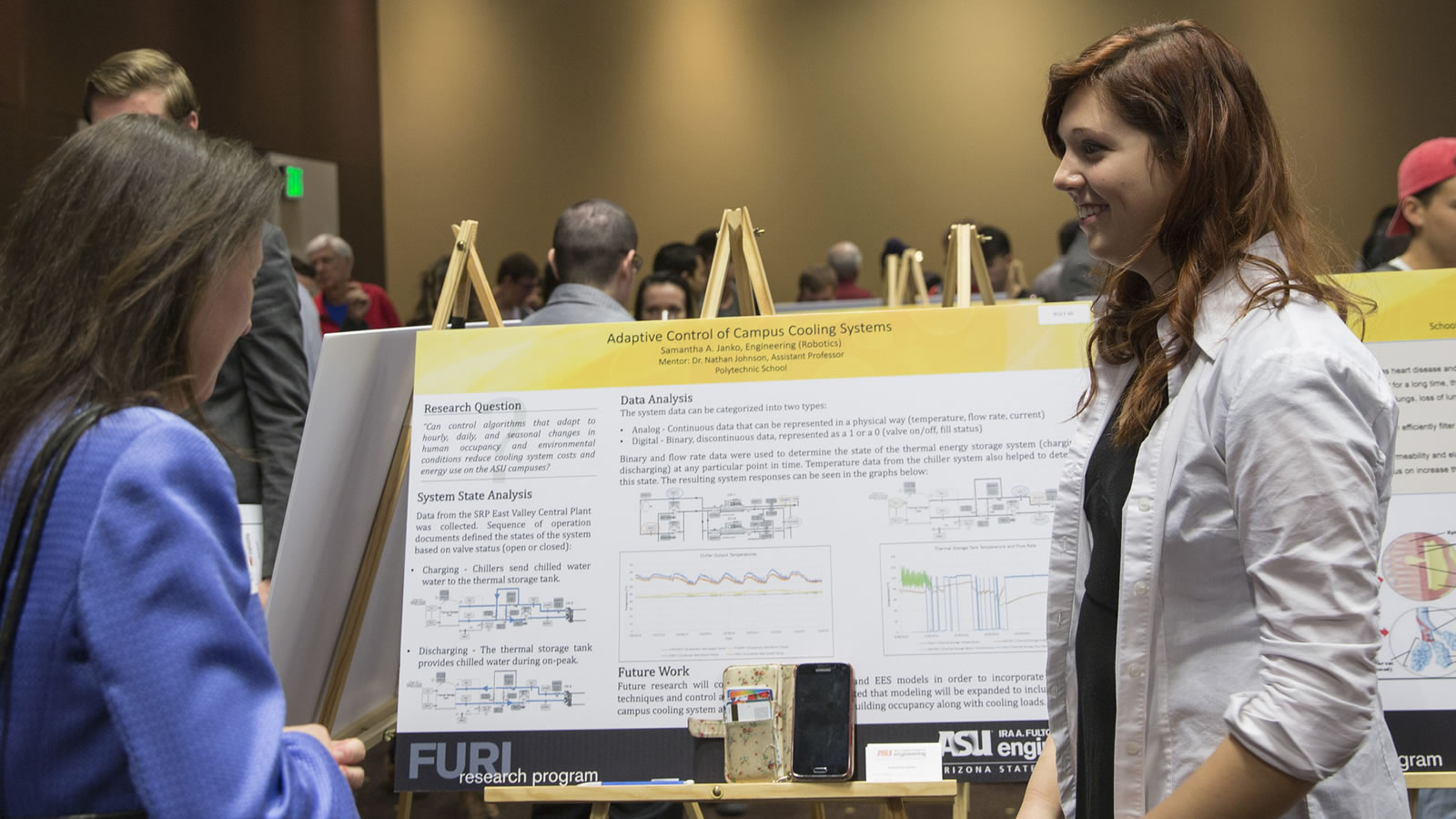 An undergraduate woman stands at her project poster display smiling at an onlooker.