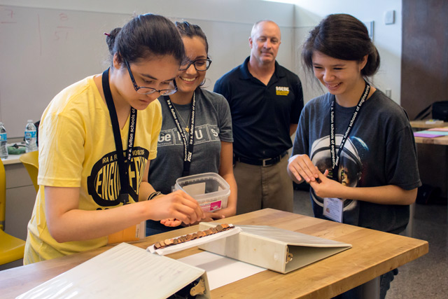Three students participate in a bridge building activity while a faculty advisor monitors their work.