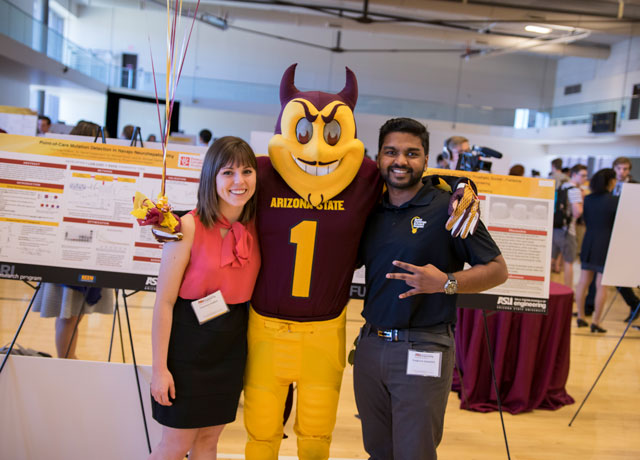 Sparky poses with two undergraduate researchers at the Fulton Undergraduate Research Initiative (FURI) Symposium.