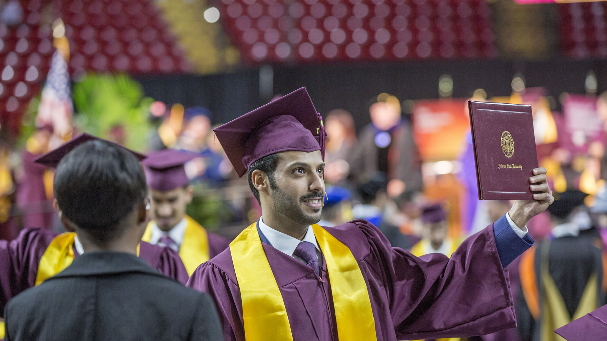 a young man holds up his diploma to the crowd during the Fulton Schools spring convocation 2017