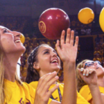 young women in a crowd with balloons falling down from above