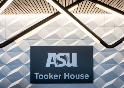 Close-up of the ASU Tooker House signage with specialized tube lighting above it.
