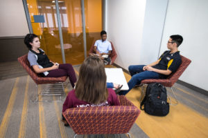 Four undergraduate friends site in a communal lounge area talking in the Tooker House.