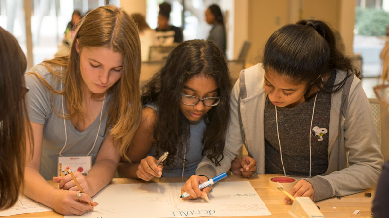 Three eighth-grade girls teamed up to work on their design for an all-in-one device that includes toothbrush, toothpaste, floss and mouthwash.
