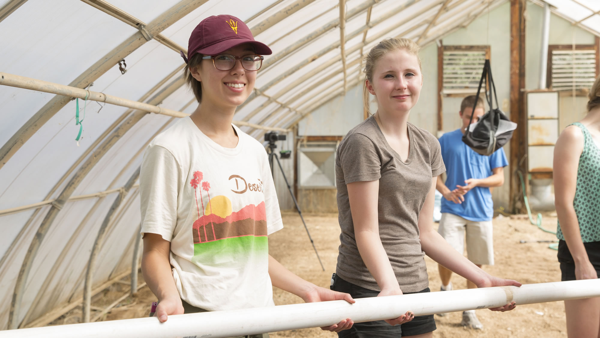 Two women students hold a PVC pipe while building an EPICS aquaponics facility
