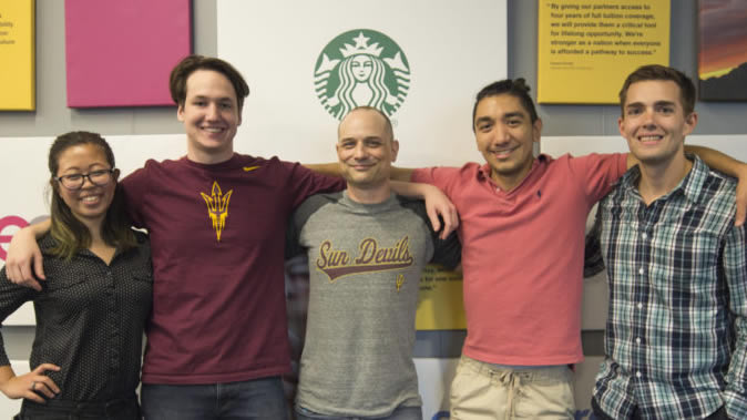 Five Starbucks interns stand arm-in-arm in front of a wall with the Starbucks logo