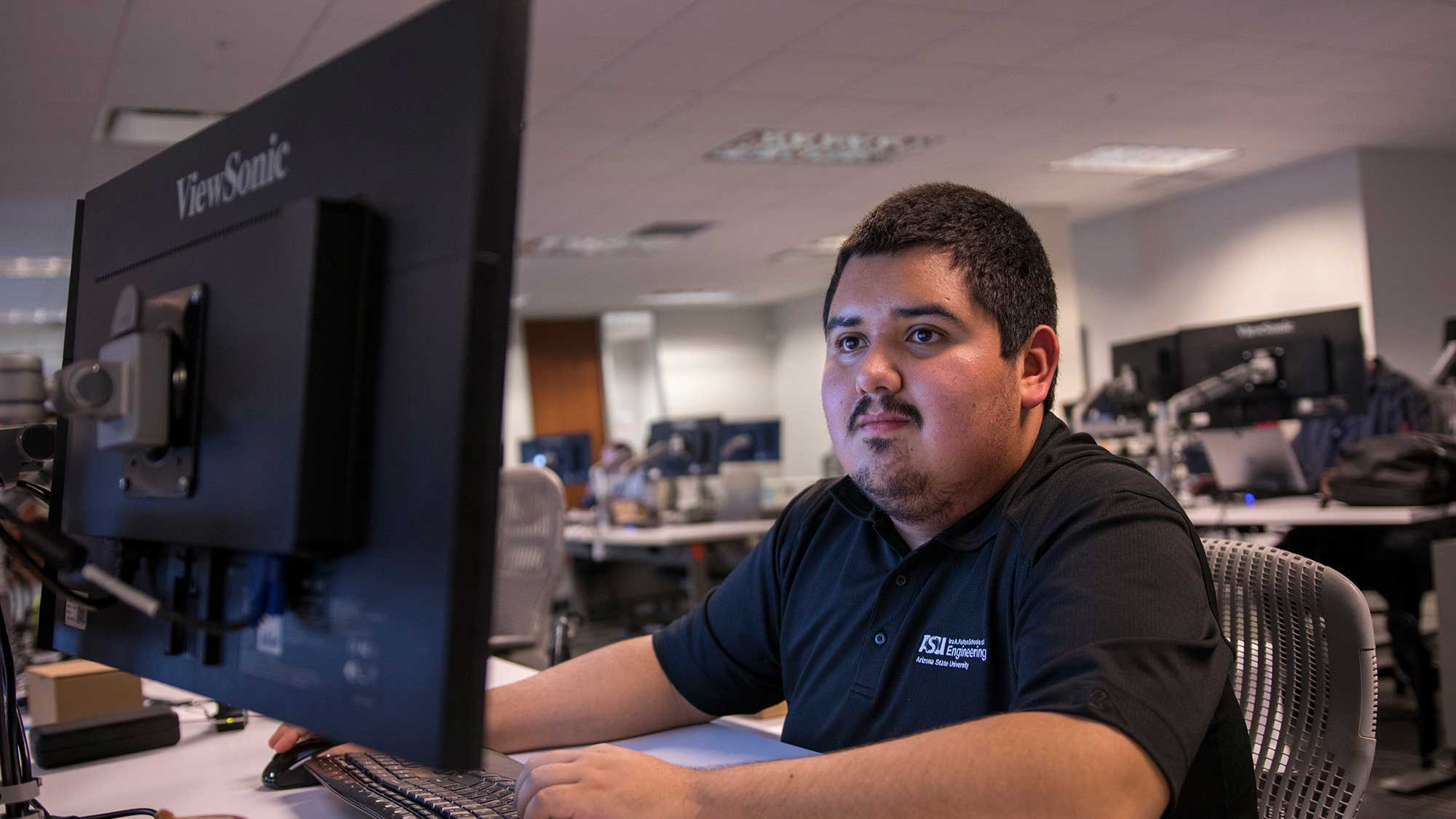 Jonathan Villegas at a computer working in a large room with many other empolyees