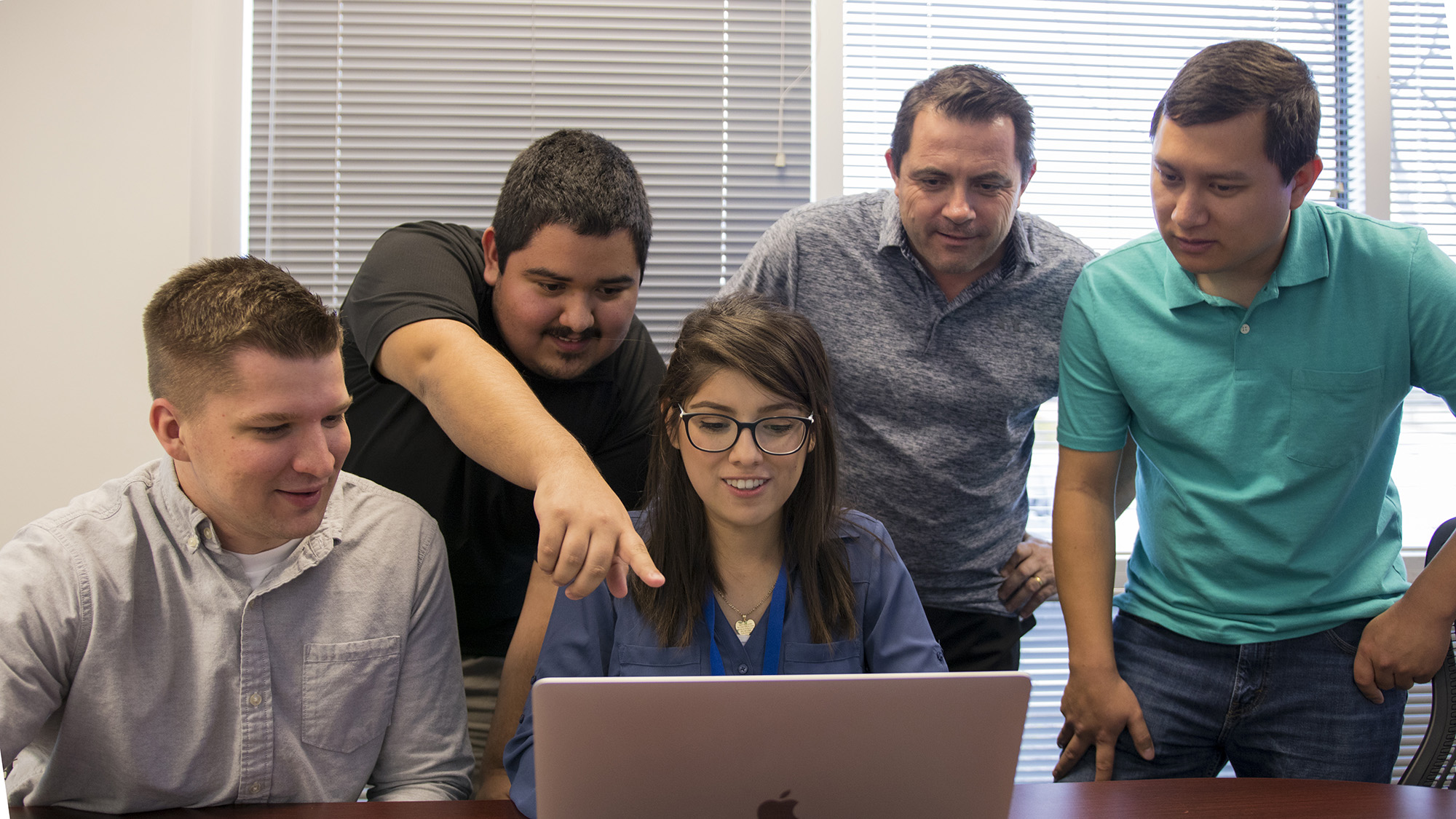 A group of 4 interns look at a laptop with their mentor in an office environment