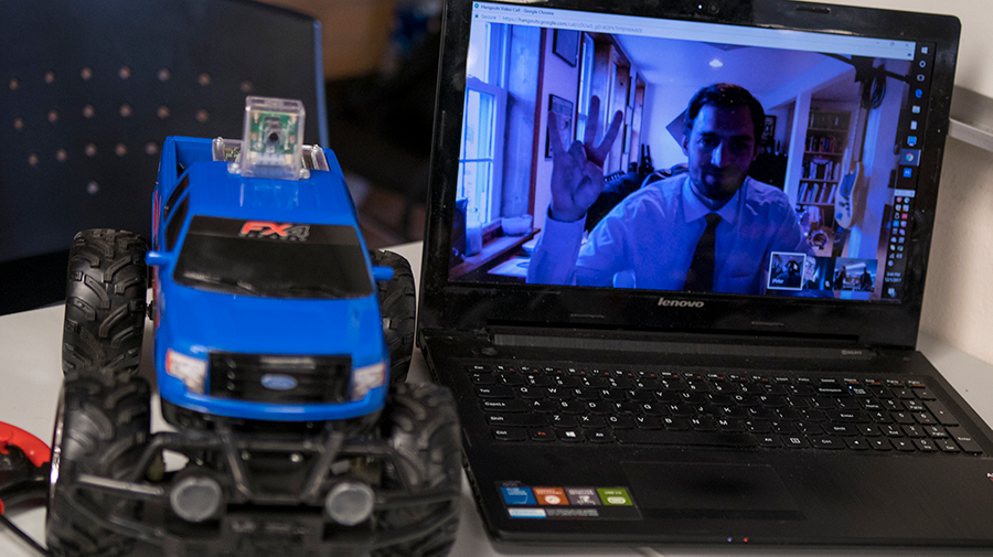 View of a student participating in an online class on the screen of a laptop next to a remote control car