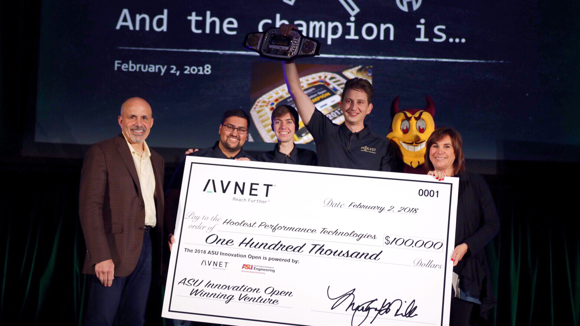 Hoolest team stand on a stage holding gigantic $100,00 prize check at the 2017 ASU Innovation Open