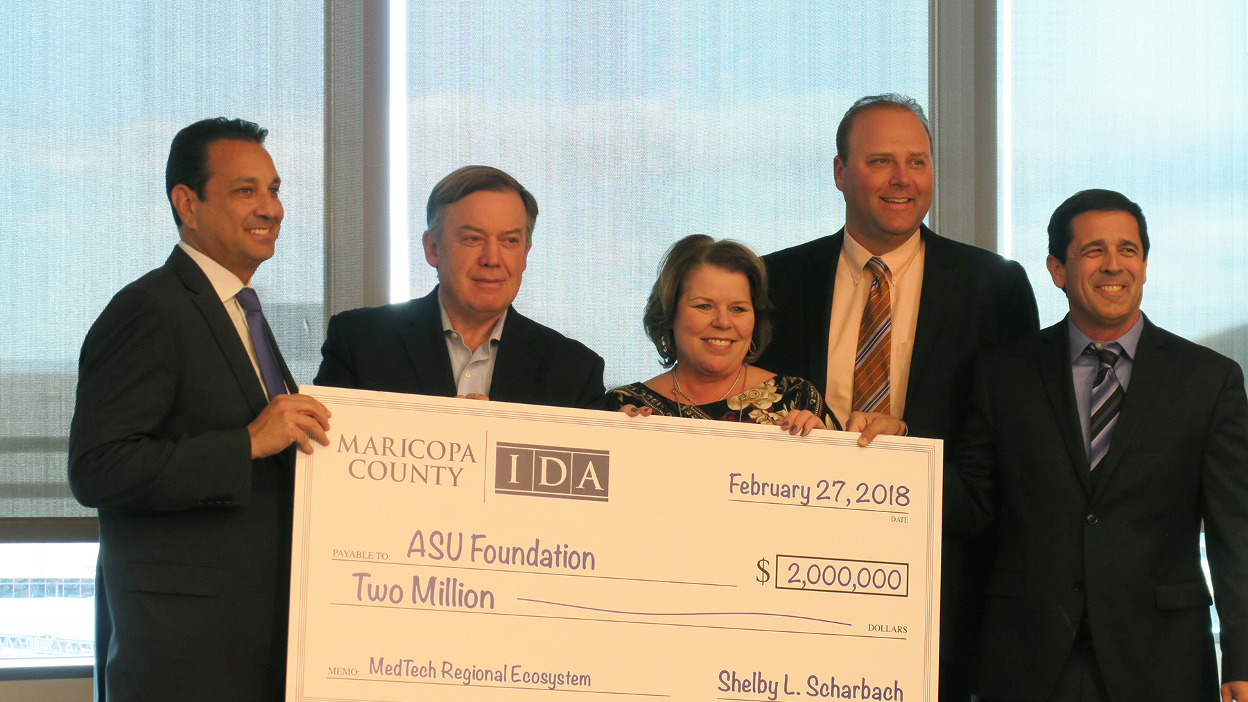 ASU President Michael Crow accepts a poster-sized $2 million check to kick off a medical technology workforce development initiation from a group of four Maricopa County executives: Steve Chucri, Shelby L. Scharbach, Jeremy Stawiecki, and Gregg Ghelfi.