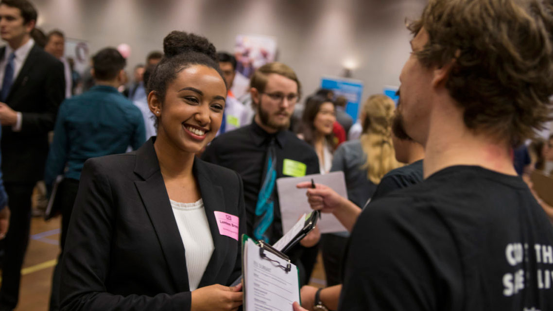 A student chats with a visiting employer at career fair.
