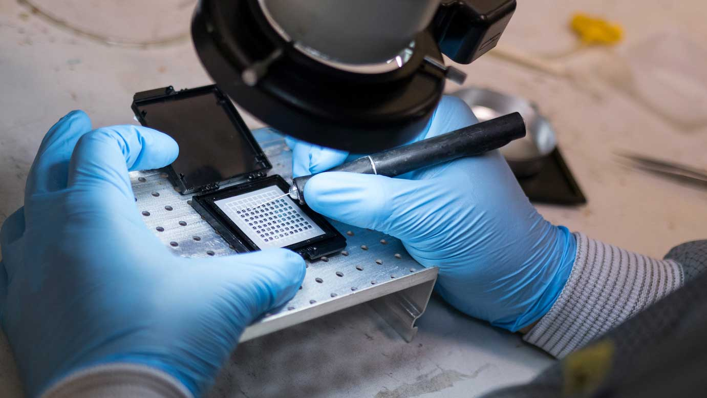 hands with blue latex gloves are shown working on a small electronic component with a fine, pointy tool.