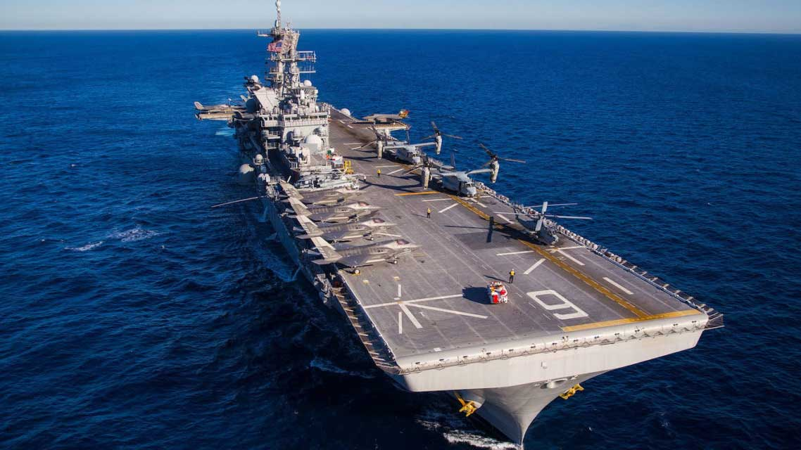 The USS America, a large air craft carrier in the ocean with several aircraft