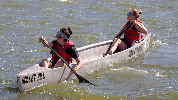 Two women paddle in a concrete canoe in the water