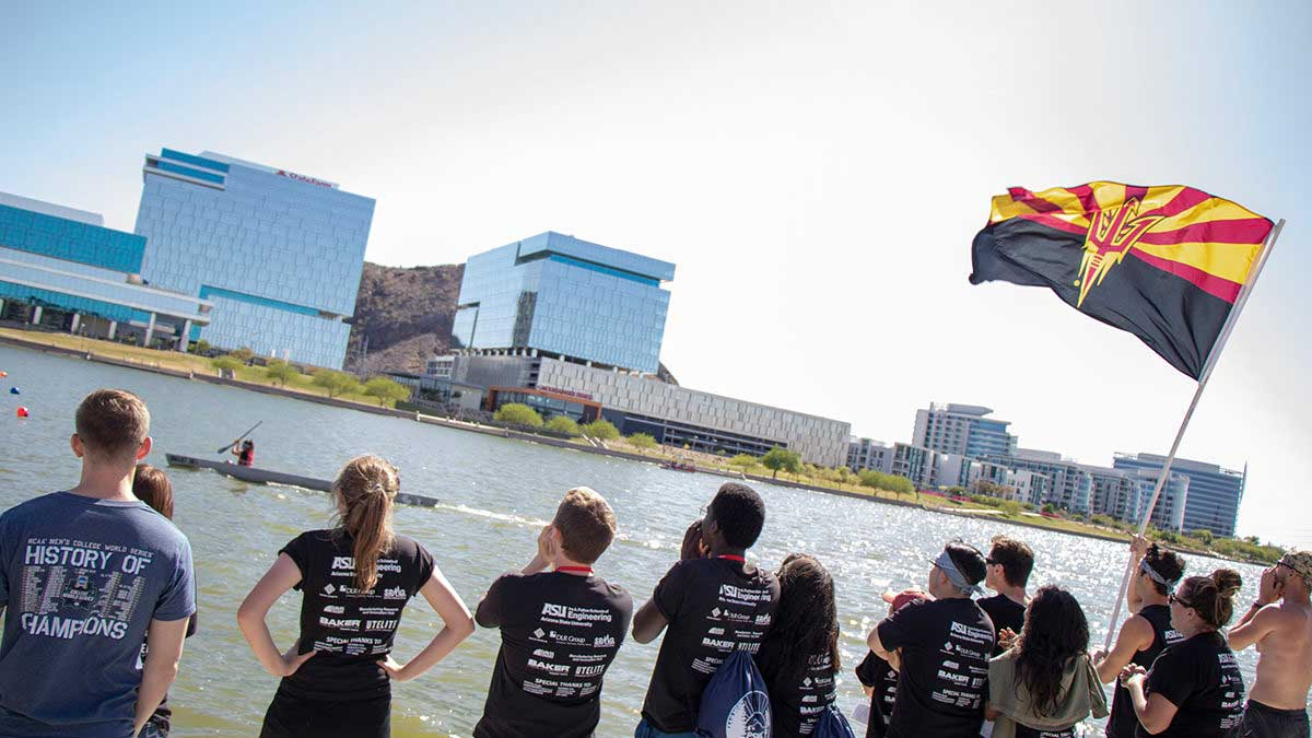 A crowd displaying an Arizona state flag with an ASU pitchfork on it cheers on a concrete canoe race at Tempe Town Lake.