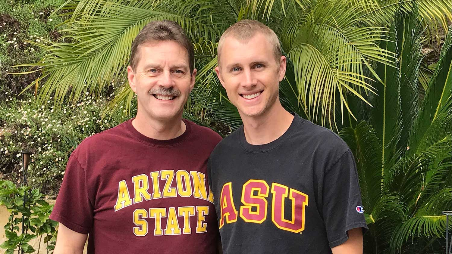 Doug Kolste, father of Brent Kolste, stand together in ASU t-shirts against palm leaves. They both graduate in May from the Fulton Schools..