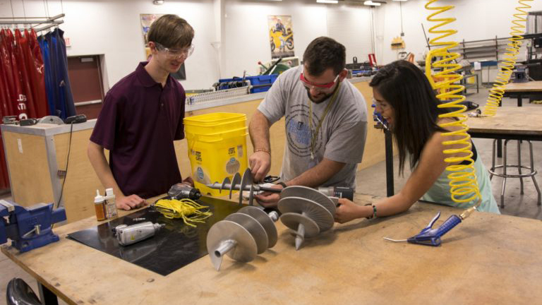 Three students work on a project at a workbench