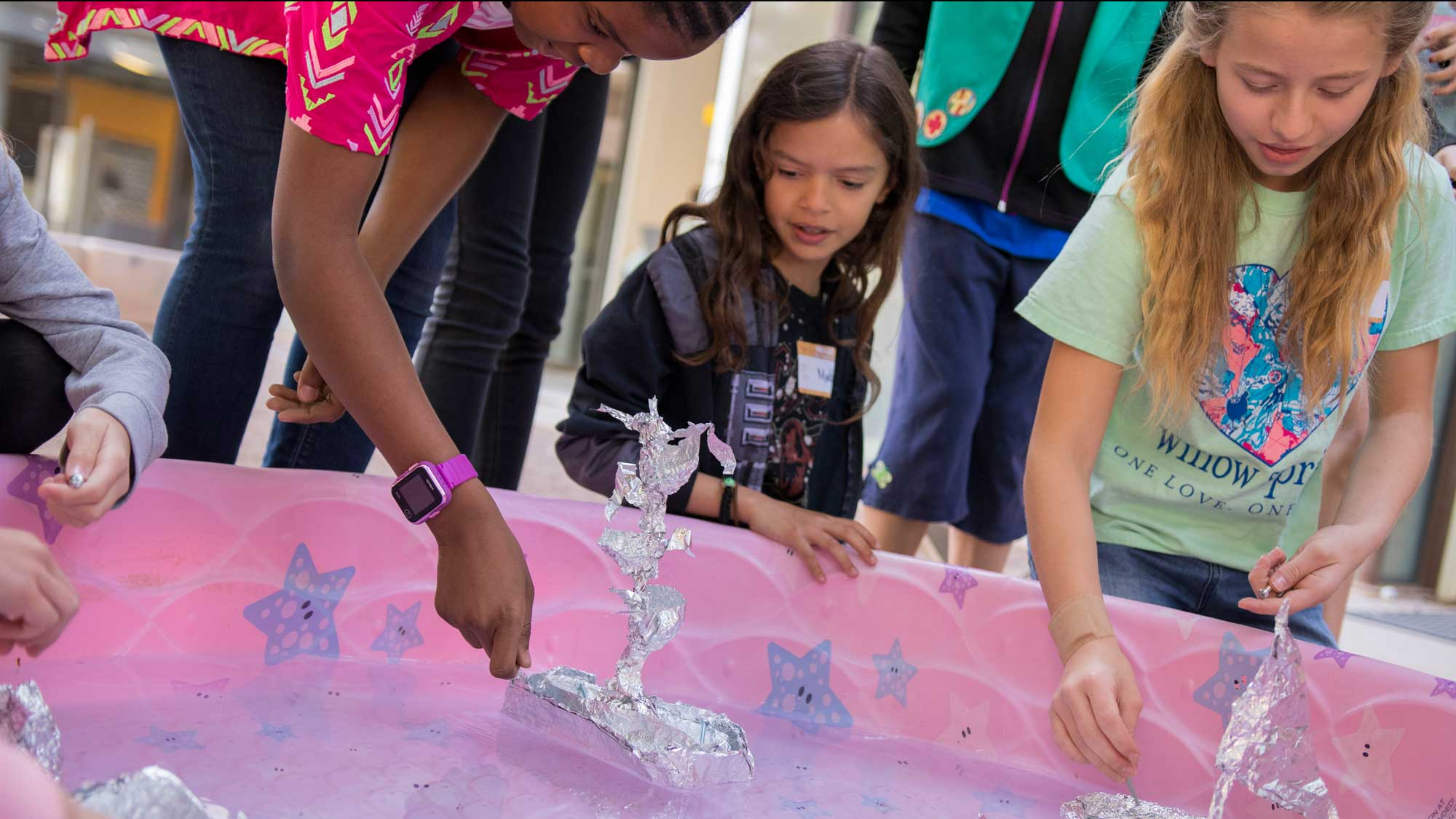 A small group of Girl Scouts sit around a kiddy pool testing out their aluminum boats.