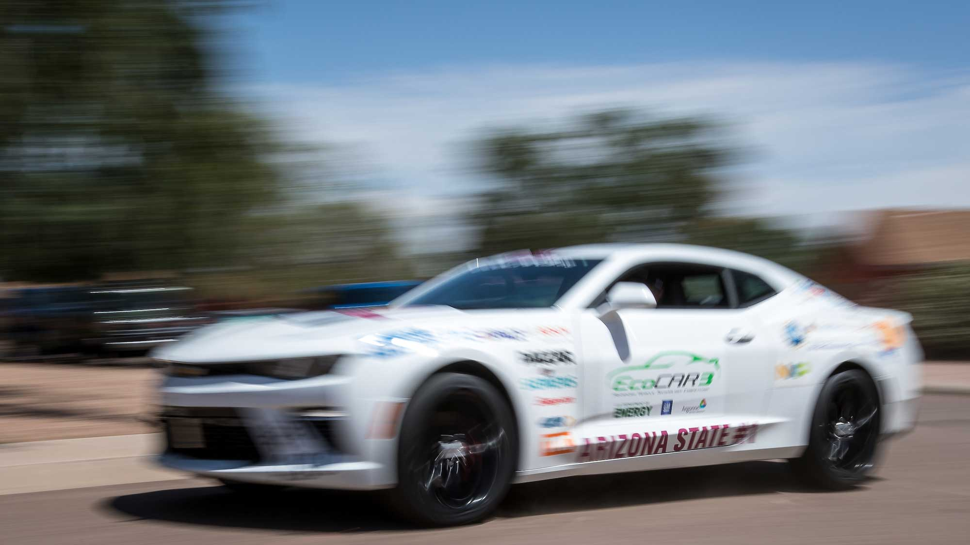 The hybrid Camero, EcoCAR3, is shown racing by in a blur
