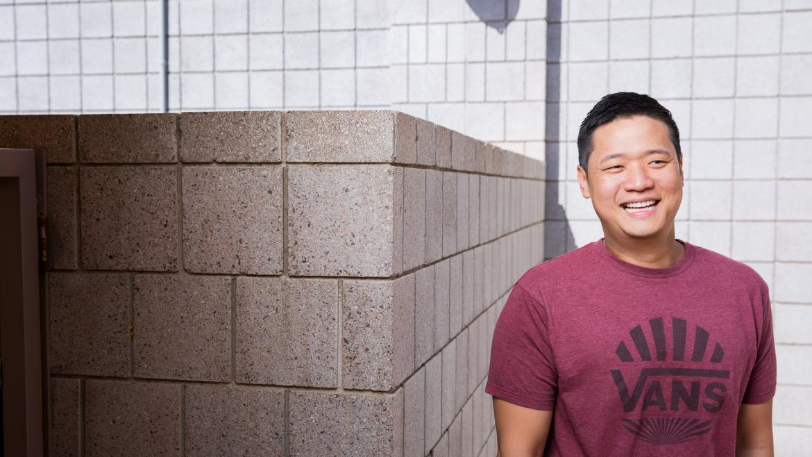 "Stefano Chang smiles for a casual photo, wearing a maroon ""Vans"" t-shirt"