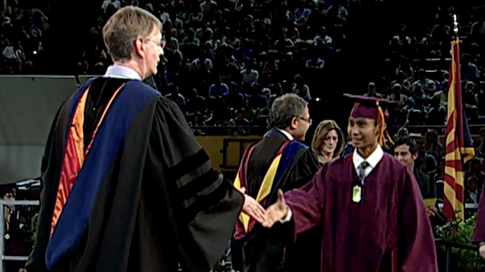 Dean Squires shakes John Cava's hand at the convocation ceremony
