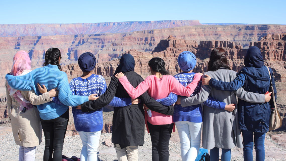 A group of US and Pakistani women students stand, arms linked, looking over the Grand Canyon