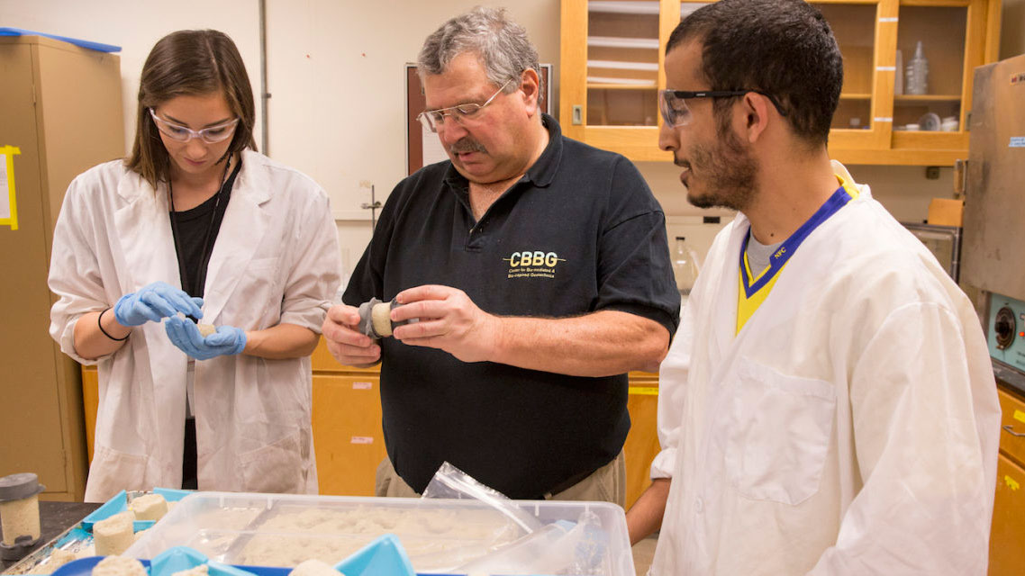 Ed Kavazanjian works in his lab with two graduate students, a woman and a man.