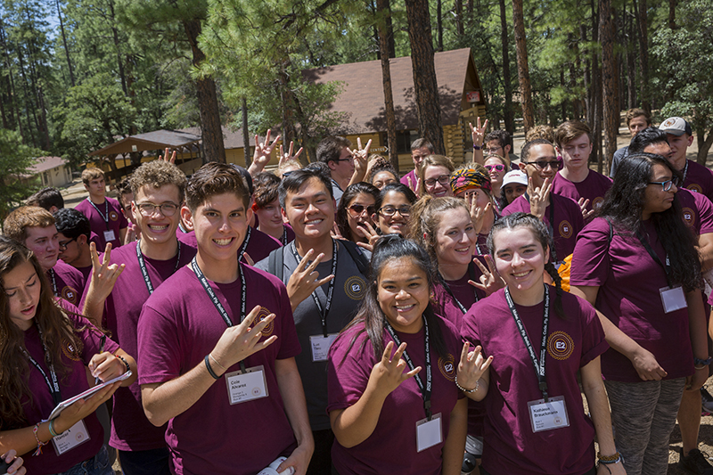 A big group of students attending E2 camp stand together smiling and making the ASU pitchfork gesture.