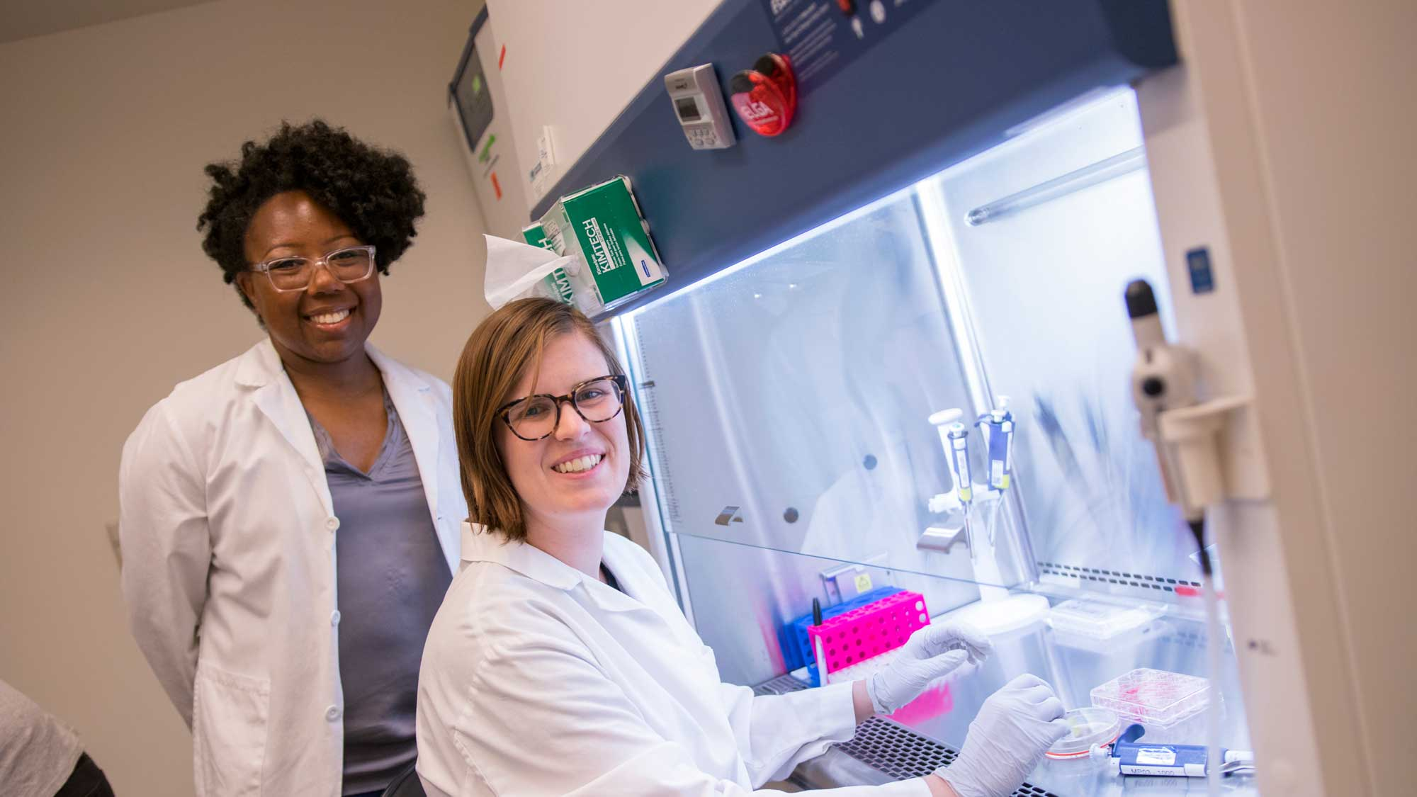 Dr. Karmella Haynes and her graduate student Cassandra Barrett sit together in the lab