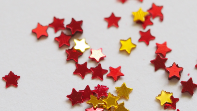 stock image of tiny maroon and gold glitter stars
