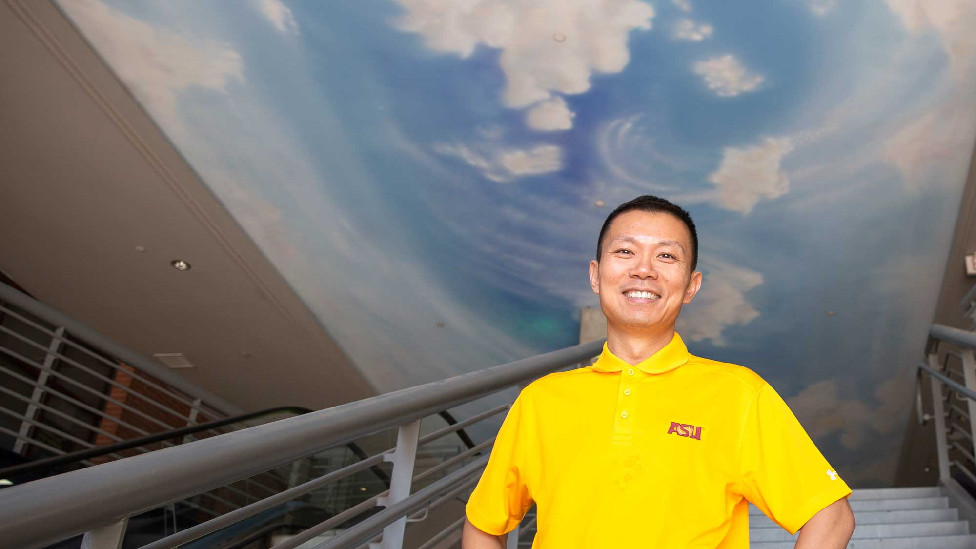 Ming Zhao stands on a staircase, hands on hips, with a sky and cloud-painted ceiling above