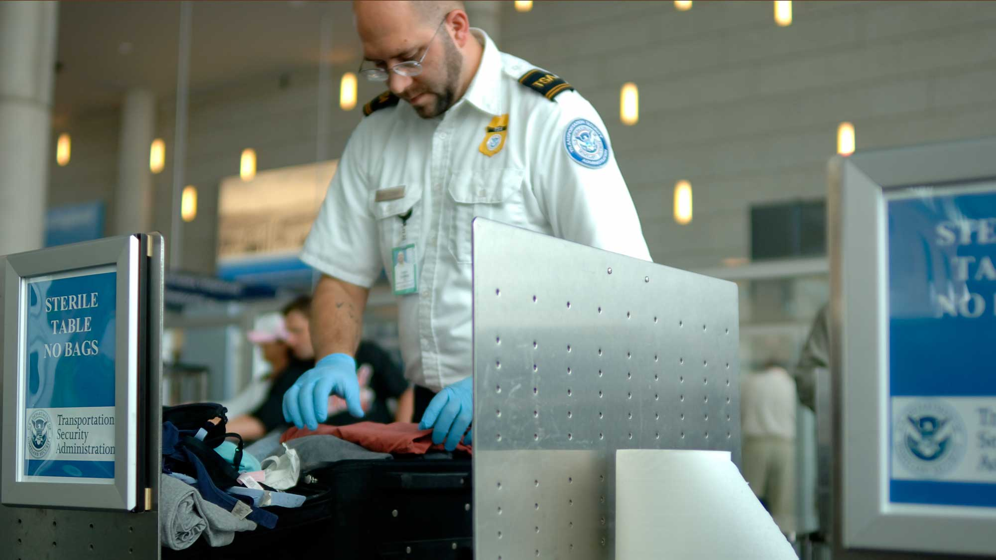 a TSA security employee searches a bag in an airport security area