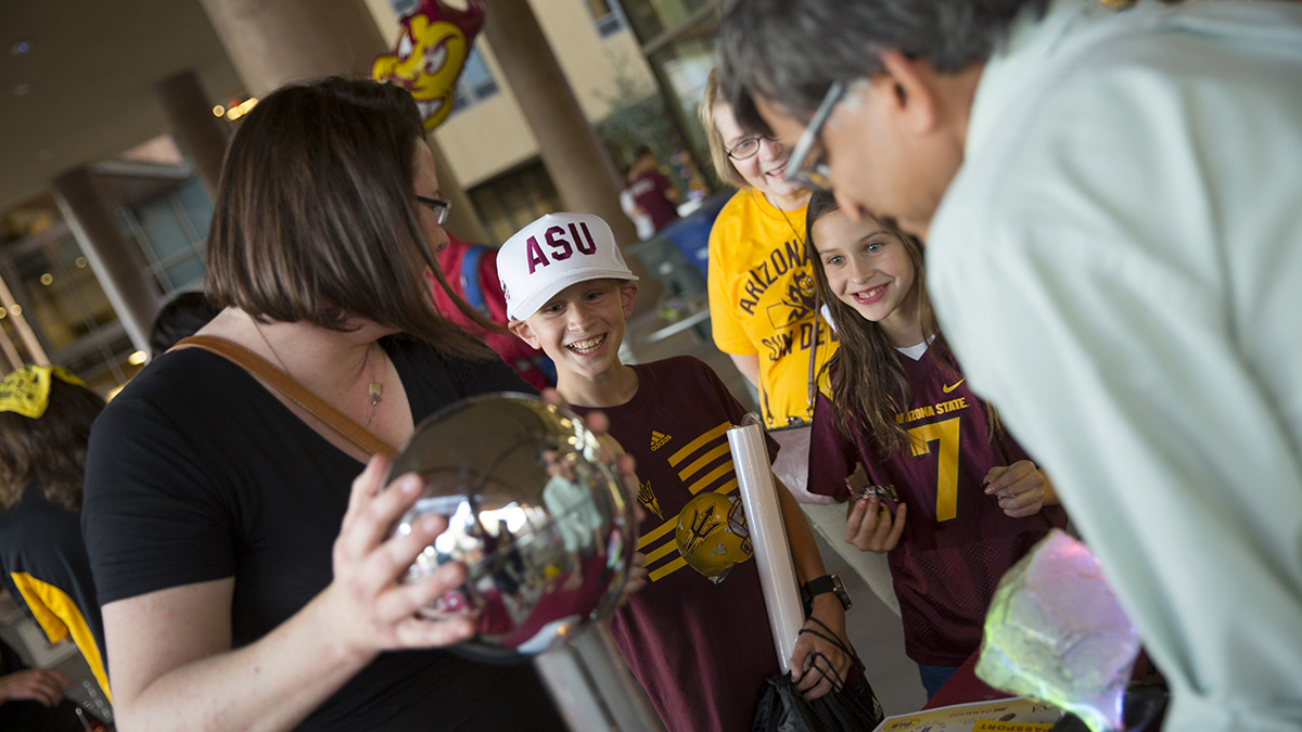 Engineering student volunteers show a group of children are shown how to use a static generator at the Fulton Schools Homecoming Block party