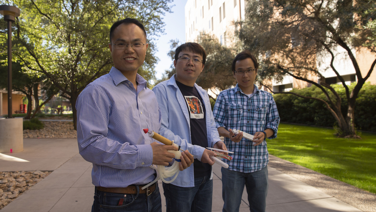 "Associate Professor Junliang ""Julian"" Tao stands outside with two PhD students, Yong Tang and Sichuan Huang, all holding 3D-printed prototypes of their clam-inspired burrower"
