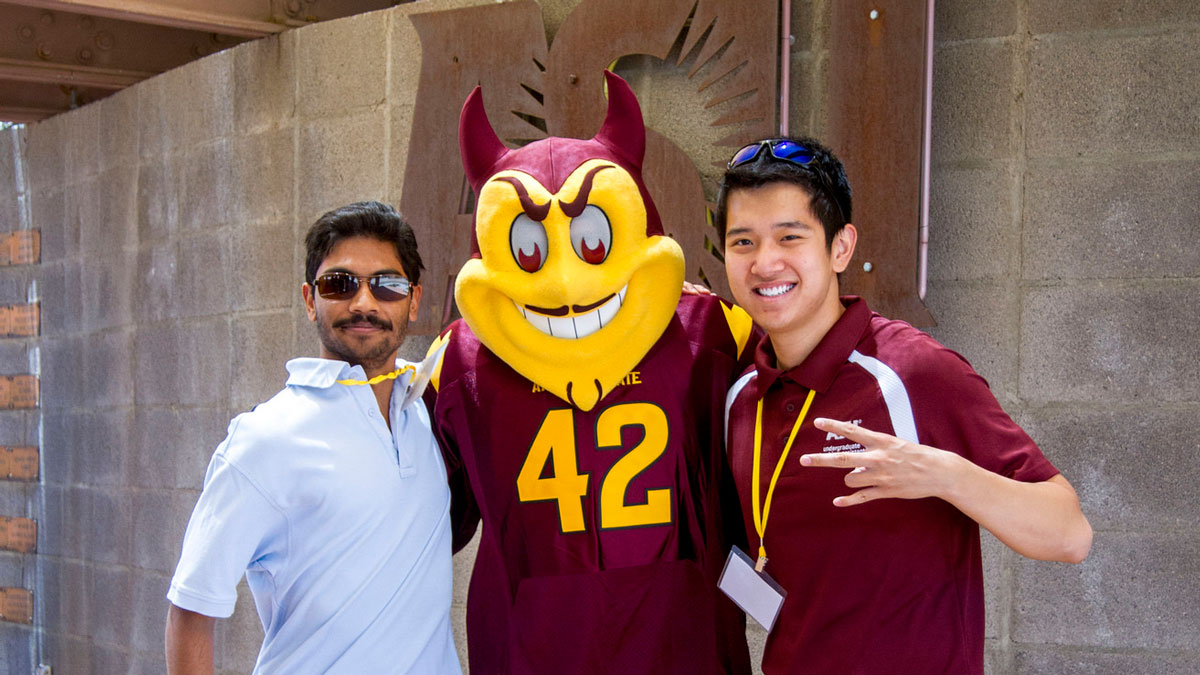 Two young men with ASU lanyards stand with Sparky at Convocation