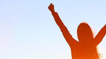 Stock image silhouette of a woman putting her arms up triumphantly