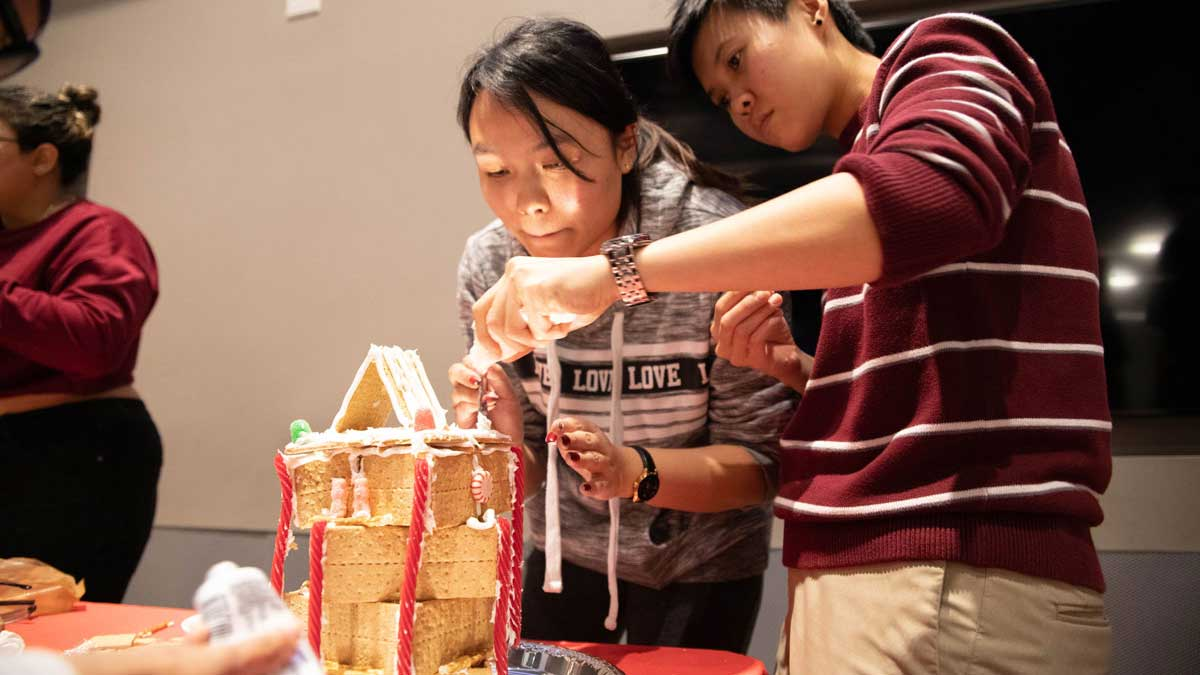 Two students work on building a gingerbread house