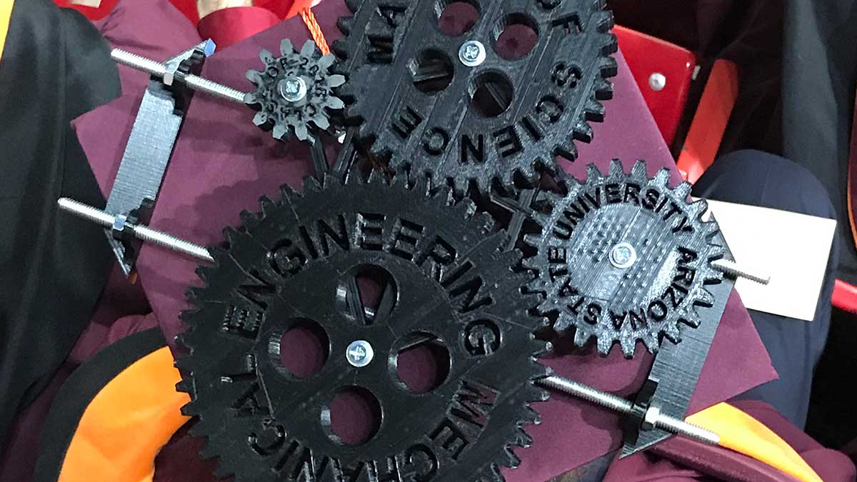 A mortarboard covered in 4 interconnected, custom black plastic gears that spell out the degree name (MS Mechanical Engineering)