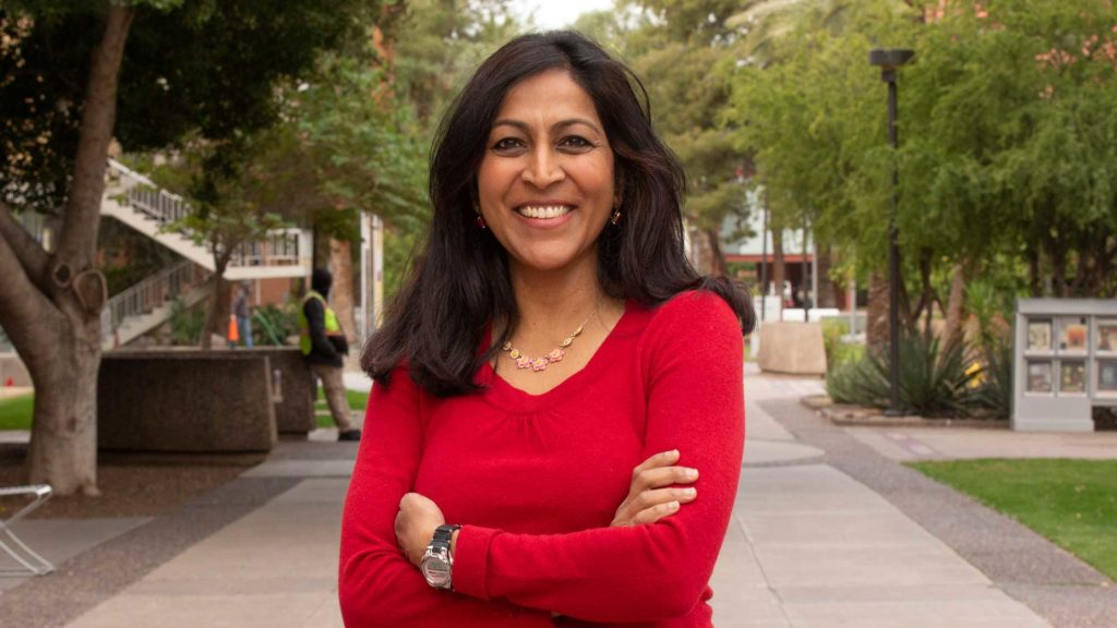 Lalitha Sankar stands outside on ASU's Tempe campus, smiling with her arms crossed.