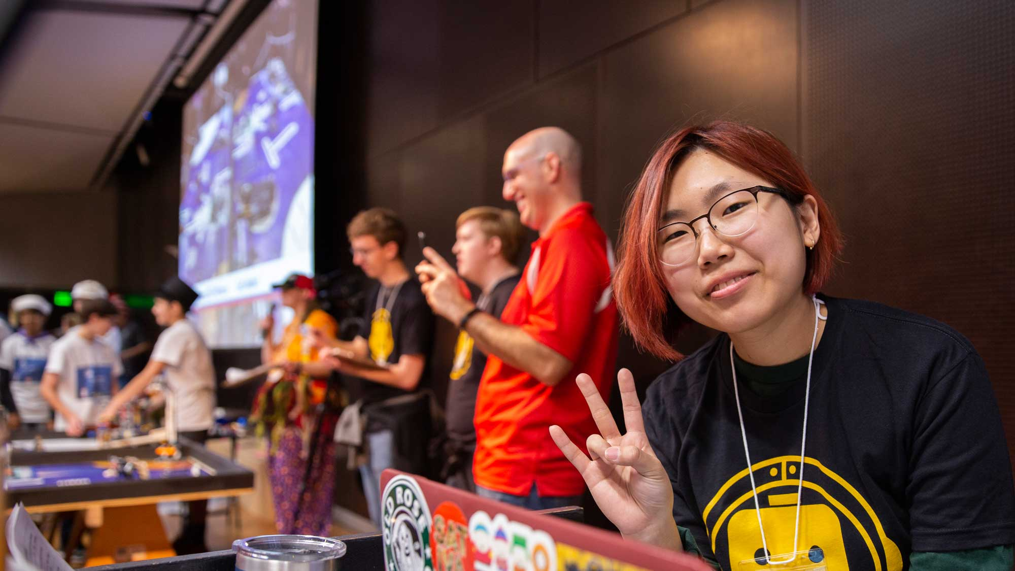 A FIRST LEGO League volunteer makes the ASU pitchfork gesture for the camera with the FLL championship happening in the background