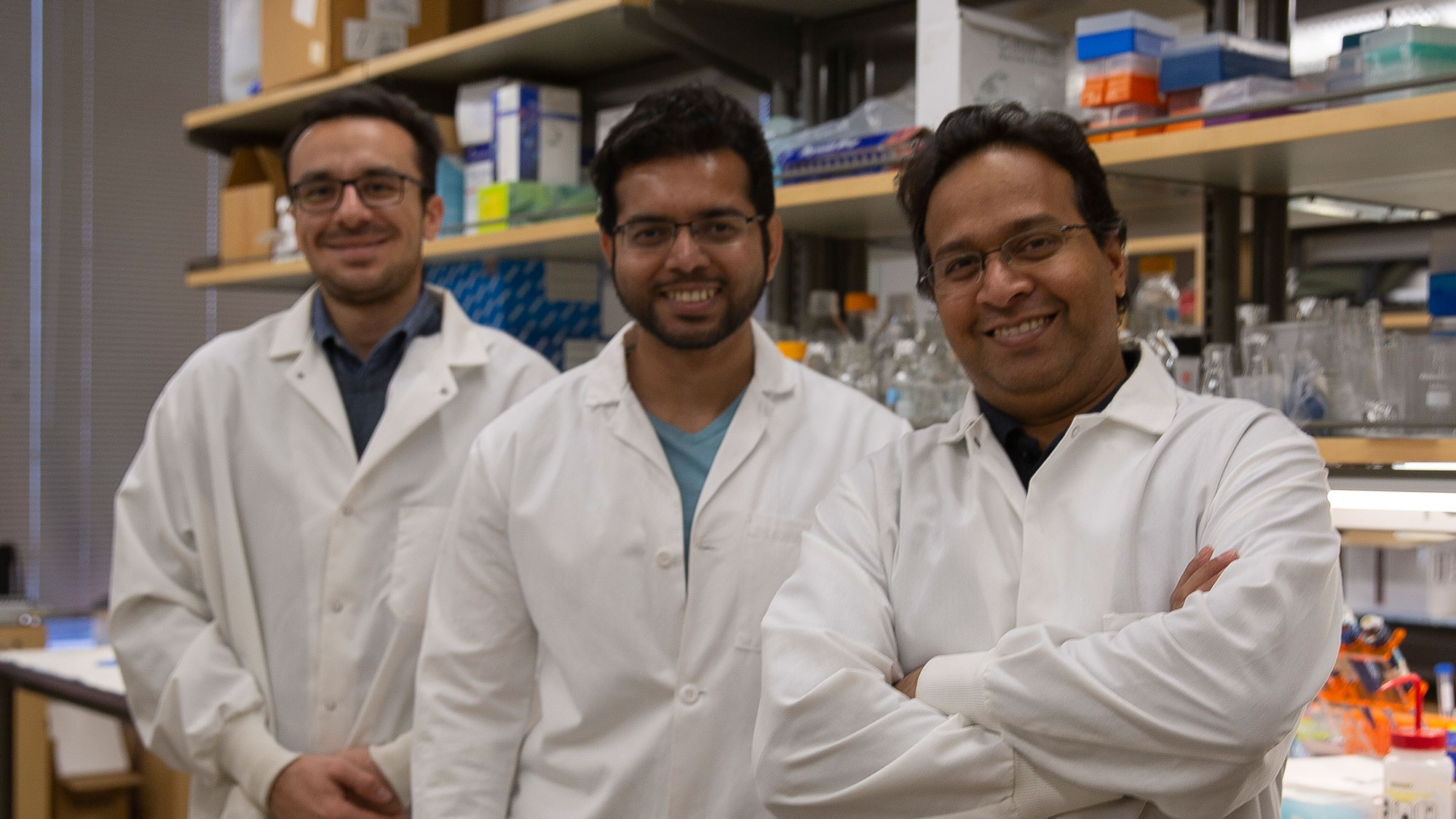 Vikram Kodibagkar stands with his two graduate students in the lab, all smiling and in lab coats.