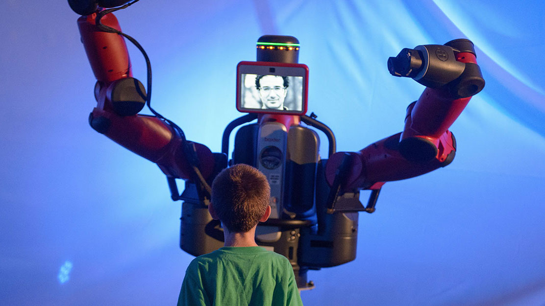 "a boy stands in front of a human-shaped robot with a screen ""face"" with a man's image on it"