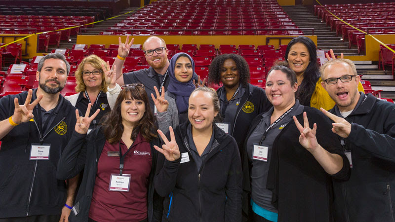 A group of convocation volunteers make the ASU pitchfork gesture and smile for the camera at Wells Fargo Arena